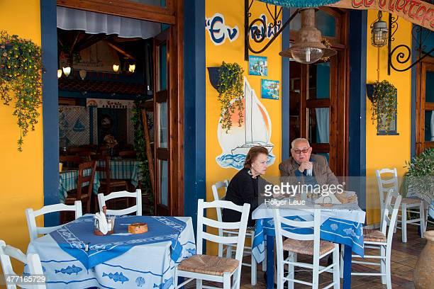 Couple sit at outdoor table at taverna