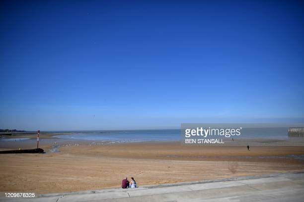 Couple sit at the near deserted beach in Margate on April 11, 2020 as warm weather tests the nationwide lockdown due to the novel coronavirus...