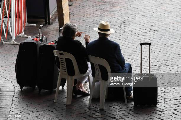 Couple sit at the Overseas Passenger Terminal after disembarking from Cunard's Queen Elizabeth on March 15, 2020 in Sydney, Australia. Carnival...