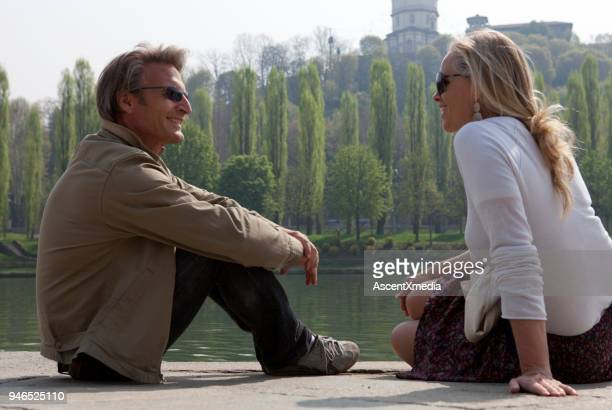 couple sit by river's edge, have conversation, turin, piedmont, italy - hand on knee stock pictures, royalty-free photos & images