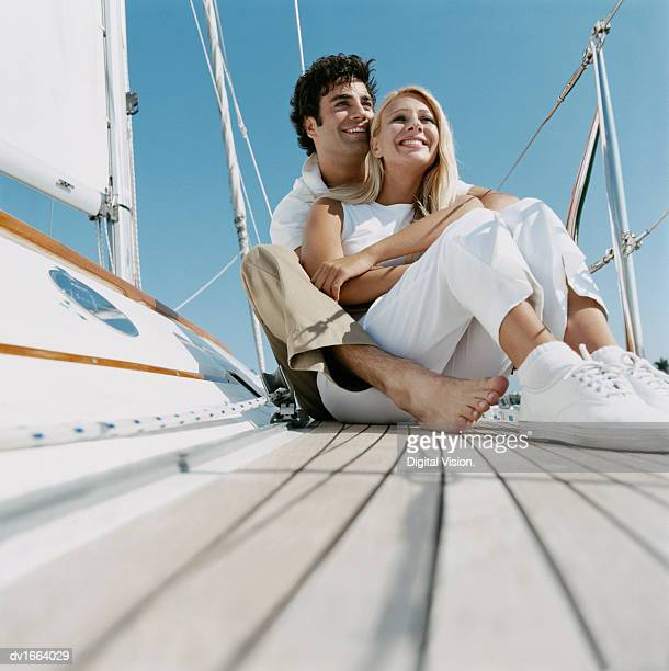 couple sit embracing on the deck of a yacht, looking at the view - pedal pushers stock pictures, royalty-free photos & images
