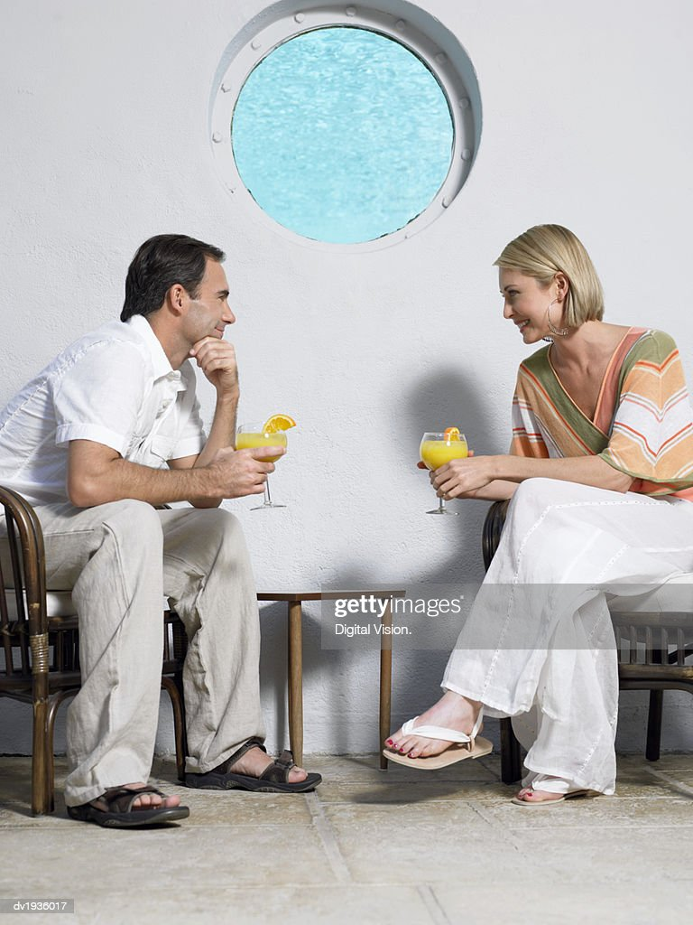 Couple Sit Face-To-Face Holding Cocktails on a Pavement Against a Wall With a Port-Hole : Stock Photo
