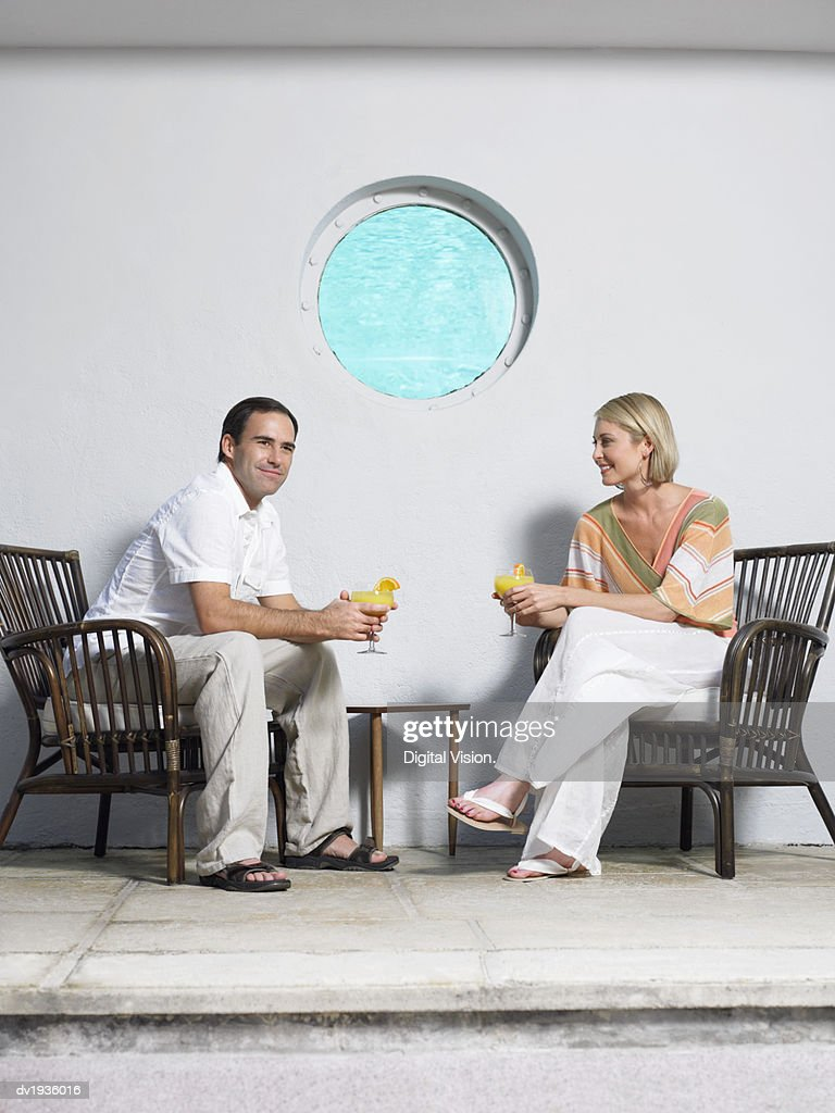 Couple Sit Holding Cocktails on a Pavement in Front of a Wall With a Port-Hole : Stock Photo