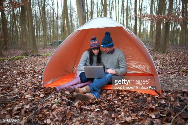 A couple sit in a tent and look at their laptop