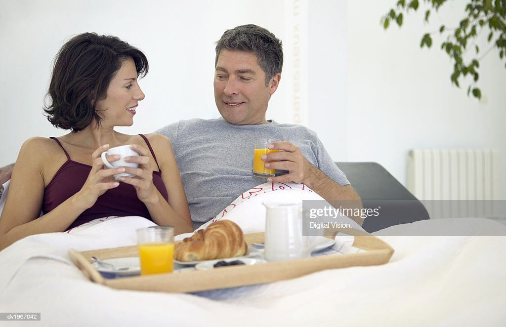 Couple Sit in Bed Having Breakfast From a Tray, Talking to Each Other : Stock Photo