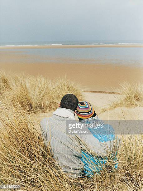 Couple Sit in Dune Grass Looking at the View to the Sea