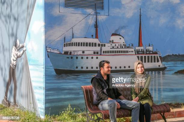 A couple sit in front of a wall displaying a mural in Ipekyolu district of Van province of Turkey on May 28 2017 Murals featuring daily life scenes...