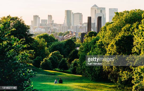 a couple sit in greenwich park, london looking the canary wharf skyline - stock photo - london stock pictures, royalty-free photos & images