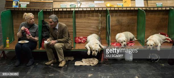 TOPSHOT A couple sit in pens next to Labrador Retrievers on the final day of the Crufts dog show at the National Exhibition Centre in Birmingham...