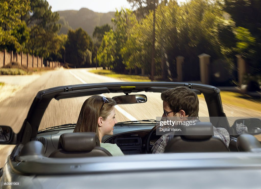 Couple Sit in the Front Seat of a Convertible, Driving on the Road and Smiling at Each Other : Stock Photo