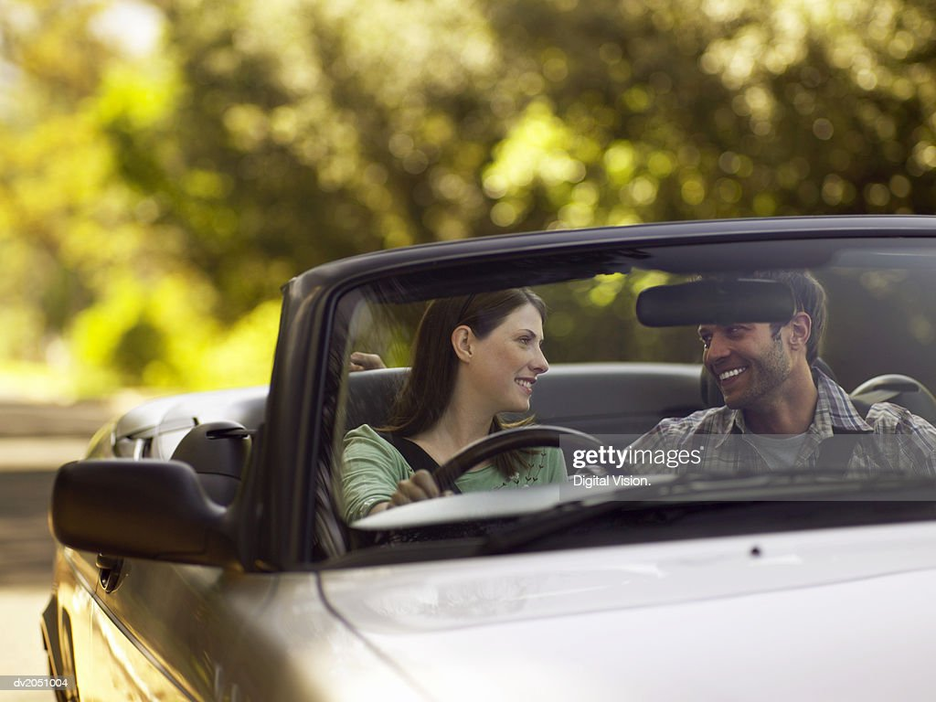 Couple Sit in the Front Seat of a Convertible, Smiling and Gazing at Each Other : Stock Photo