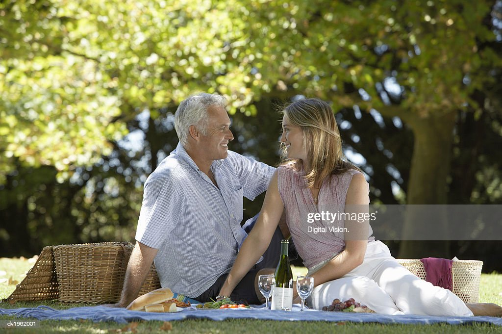 Couple Sit in the Park Having a Picnic, Gazing into Each Other's Eyes : Stock Photo