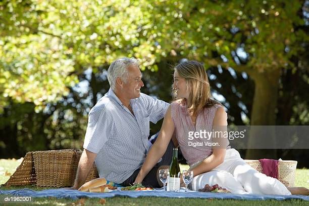 Couple Sit in the Park Having a Picnic, Gazing into Each Other's Eyes