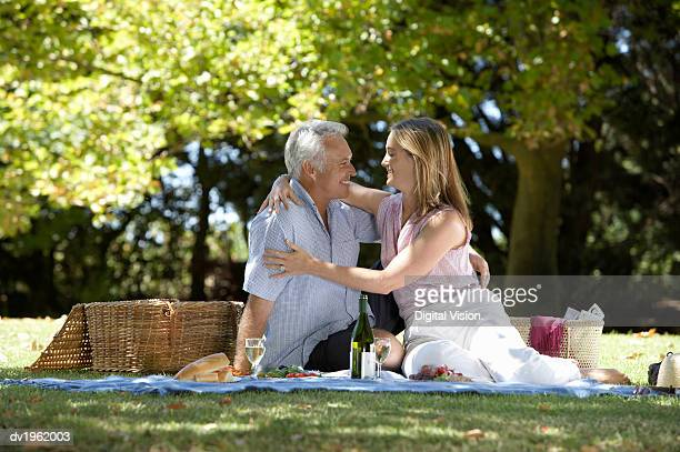 couple sit in the park having a picnic, gazing into each other's eyes and embracing - may december romance stock photos and pictures