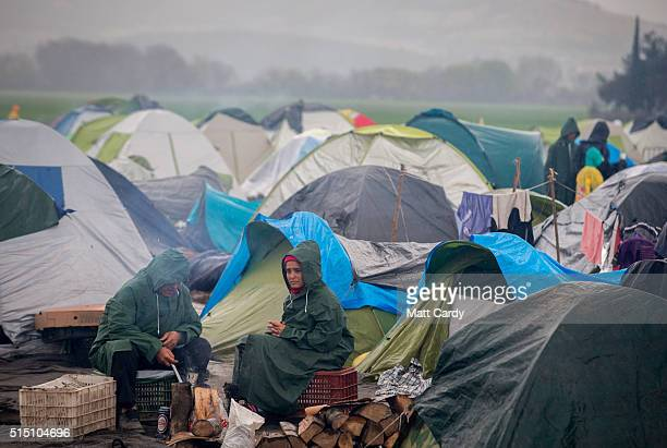 A couple sit in the rain besides their tent at the Idomeni refugee camp on the Greek Macedonia border on March 12 2016 in Idomeni Greece The decision...