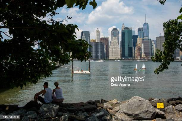 Couple sit in the shade along the shoreline in Brooklyn Bridge Park, July 20, 2017 in the Brooklyn borough of New York City. Thursday is forecasted...