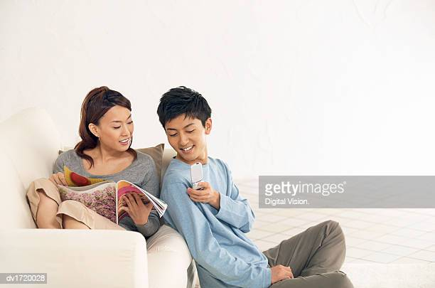 Couple Sit in Their Home, Woman on the Sofa With a Magazine, Her Boyfriend Showing Her His Mobile Phone