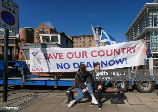 A couple sit on a bench as a 30ft fishing boat on a lorry drives past as part of the Fishing For Leave protest at the Quayside area of the River Tyne...