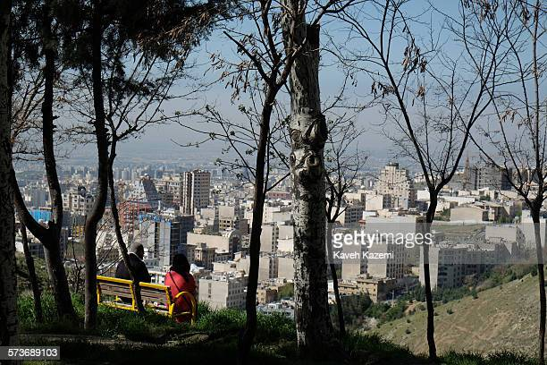 Couple sit on a bench enjoying the city view and fresh air on the Tochal hills on April 15, 2015 in Tehran, Iran. Tochal is located on the north...
