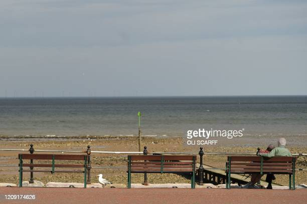 A couple sit on a bench in the fine weather in Llandudno north Wales on April 5 2020 as the warm weather tests the nationwide lockdown to combat the...