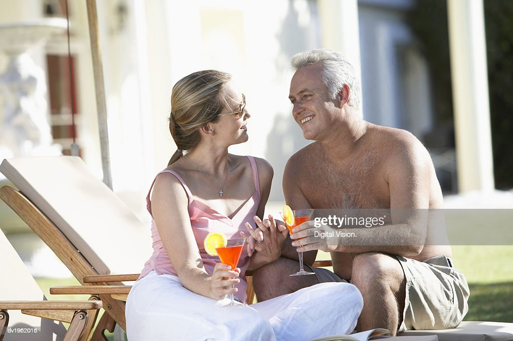 Couple Sit on a Sun Lounger Holding Cocktail Glasses and Gazing at Each Other : Stock Photo