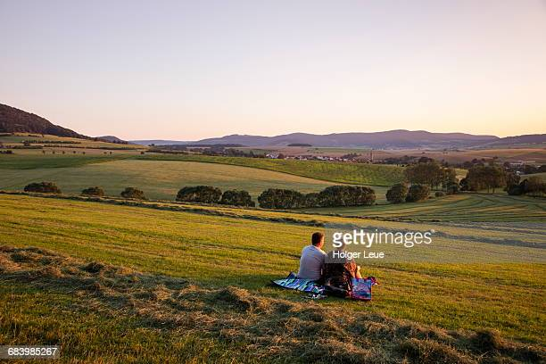couple sit on blanket in meadow at sunset - テューリンゲン州 ストックフォトと画像