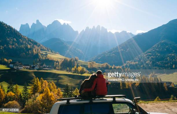 Couple sit on car rooftop looking at mountains in the distance