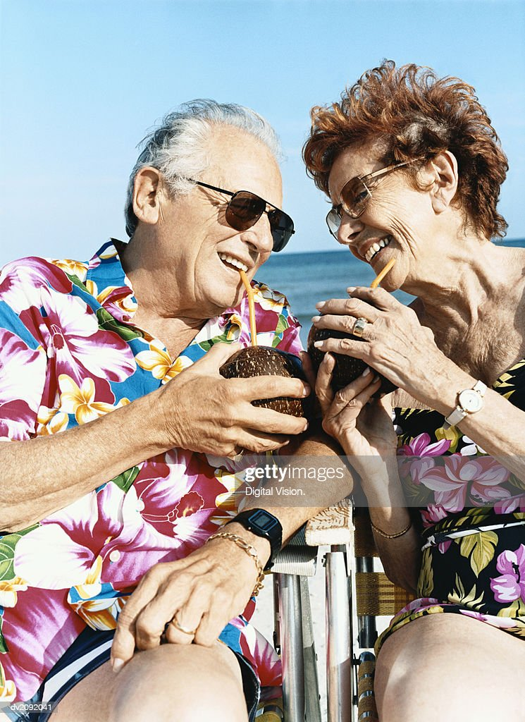 Couple Sit on Chairs Looking Face to Face and Drinking With a Straw From Coconuts : Stock Photo