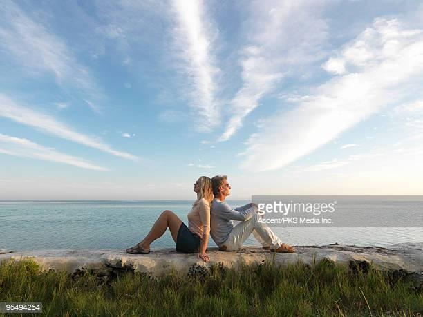 couple sit on rocks above sea, facing opposite way - 背中合わせ ストックフォトと画像