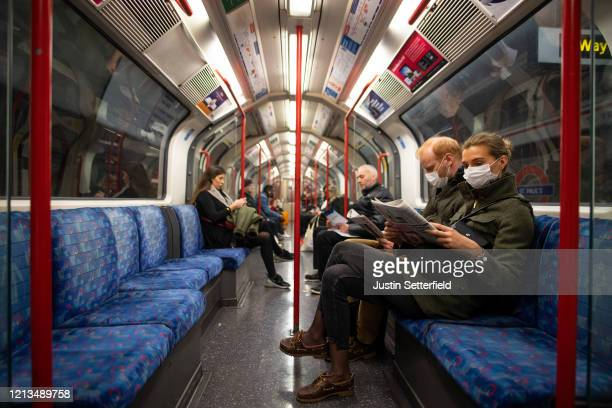 A couple sit on the Central Line Tube wearing protective face masks while reading a newspaper on March 19 2020 in London England Transport for London...