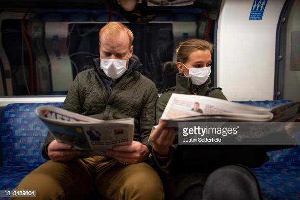 Couple sit on the Central Line Tube wearing protective face masks while reading a newspaper on March 19, 2020 in London, England. Transport for...