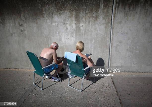 A couple sit on the sea front facing the sea wall on September 29 2011 in Canvey Island England Much of the United Kingdom is enjoying a late spell...