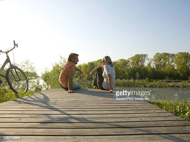 Couple sit on wooden dock over river, with bicycle