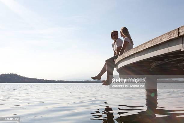 Couple sit on wooden dock,dangle feet towards lake