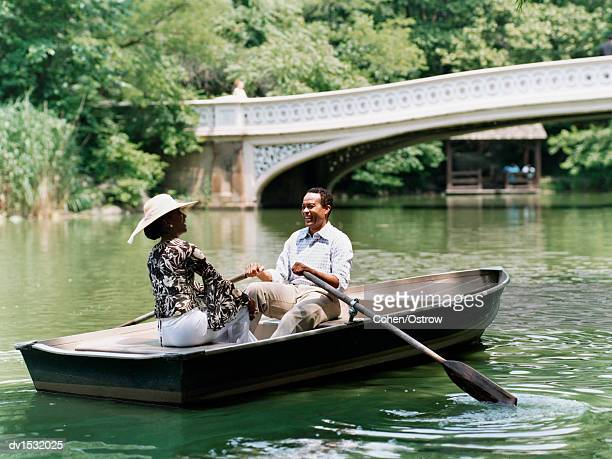 Couple Sit Opposite Each Other in a Rowing Boat on a River in Central Park, Laughing