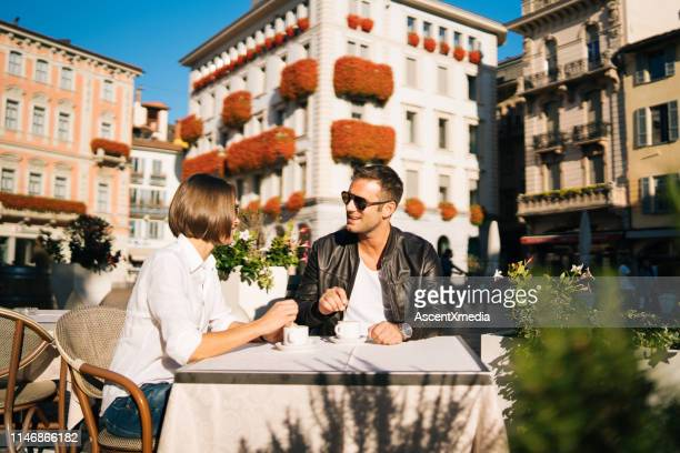 Couple sit outdoors at cafe in town square