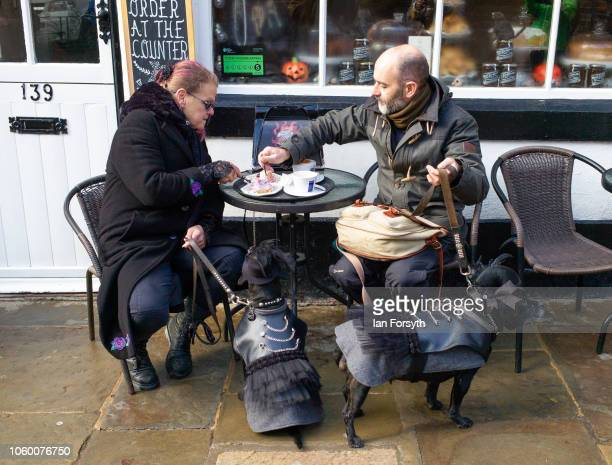 A couple sit outside a cafe with their dogs dressed in goth clothing during Whitby Goth Weekend on October 27 2018 in Whitby England The Whitby Goth...
