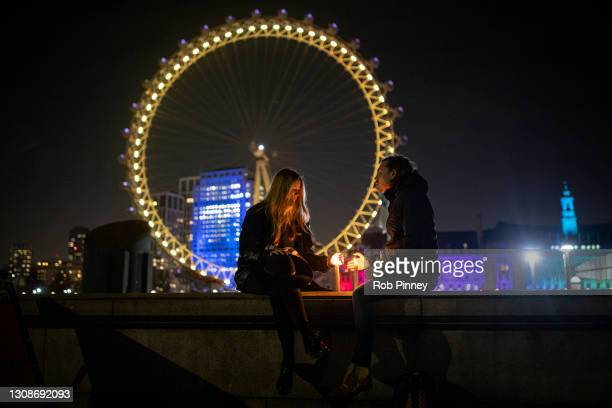 Couple sit with candles on a wall opposite the London Eye which is illuminated yellow on March 23, 2021 in London, England. Marie Curie Cancer...