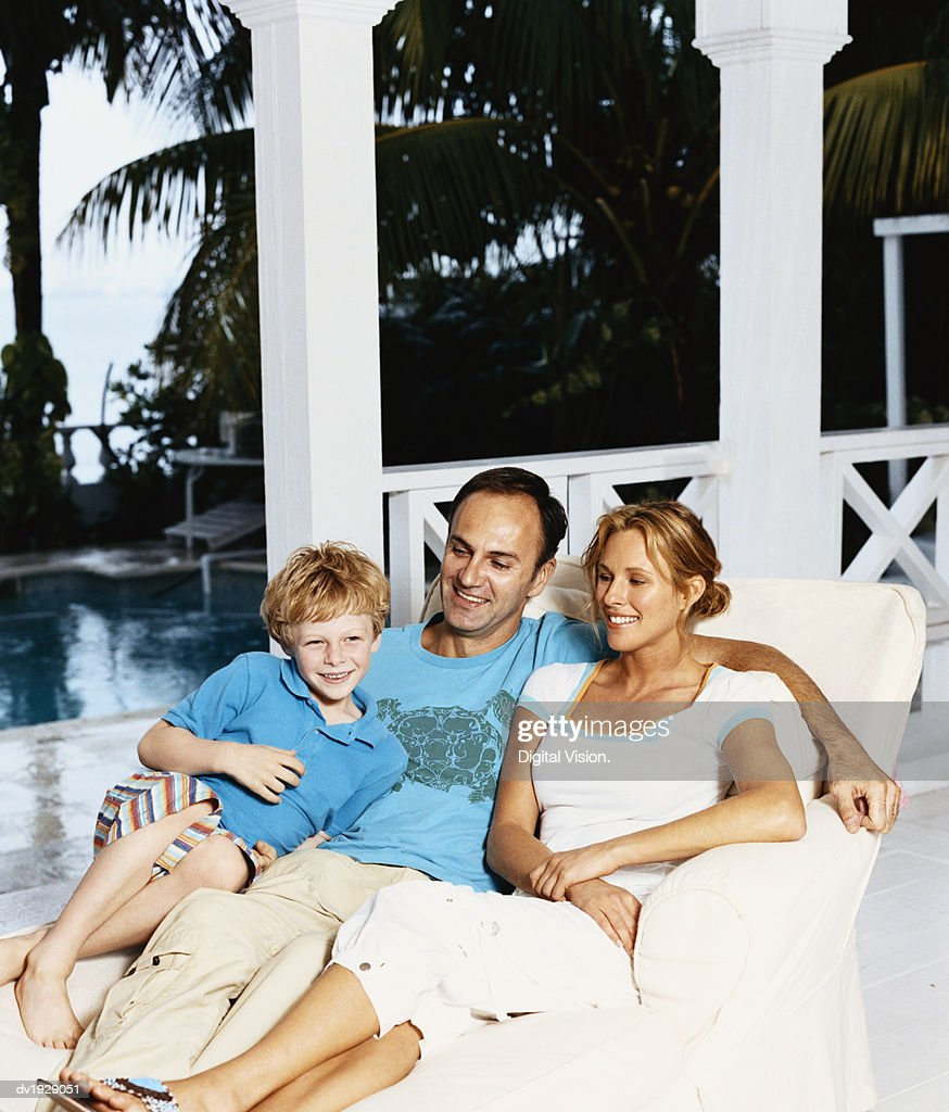 Couple Sit With Their Young Son on a Lounger Chair on Their Porch : Stock Photo
