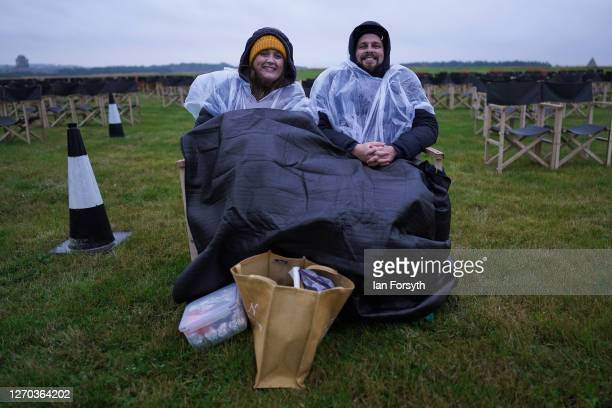 Couple sit wrapped in blankets and plastic ponchos as members of the public attend a screening of The Greatest Showman during the Luna Cinema movie...