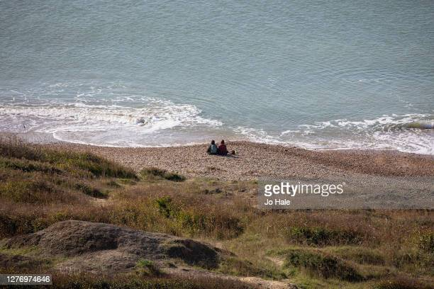 Couple siting on the beach in Barton in the New Forest on September 27, 2020 in Hampshire, England.