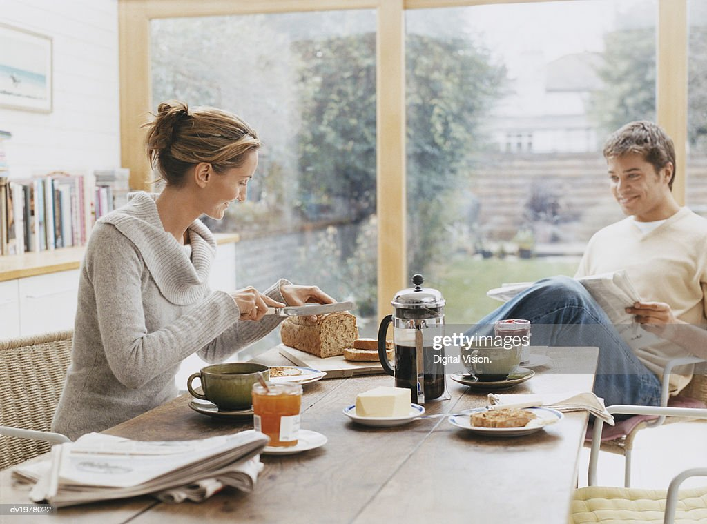 Couple Sits at a Kitchen Table Having Breakfast : Foto de stock