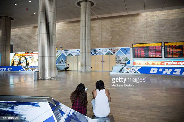 A couple sits at an empty arrivals gate at terminal three of Ben Gurion Airport on July 24 2014 in Tel Aviv Israel The Federal Aviation...