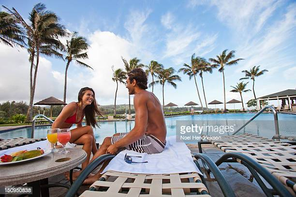 A couple sits by the pool with fresh snacks
