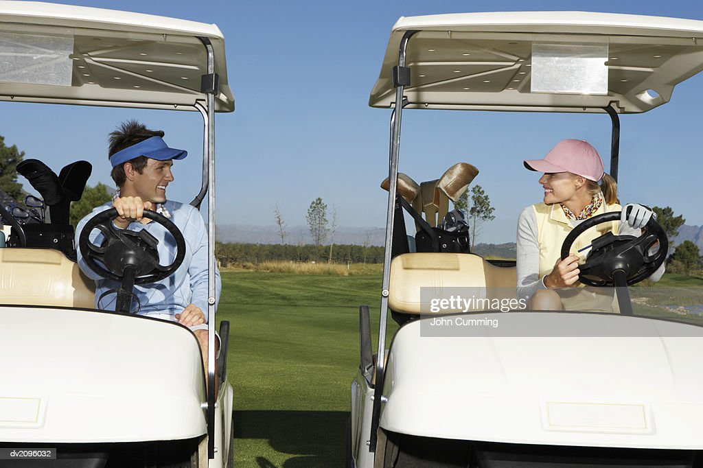 Couple Sits in Golf Buggies Looking Face to Face : Stock Photo