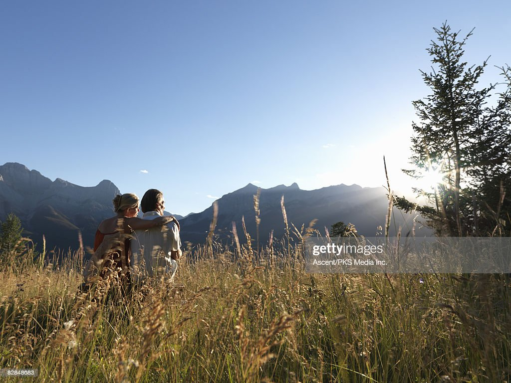 Couple sits in grassy mountain meadow at sunset : Bildbanksbilder