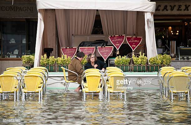 A couple sits in St Mark's Square during today first high tide of the season in Venice with water reaching the level at sea of 110 centimetres above...