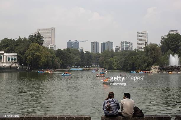 A couple sits near an artificial lake as visitors operate paddle and row boats inside the first section of Chapultepec Park in Mexico City Mexico on...