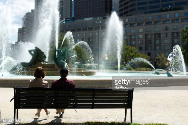 A couple sits on a bench near the fountain on Logan Square as the Parkway100 centennial celebration kicks off at the Benjamin Franklin Parkway in...