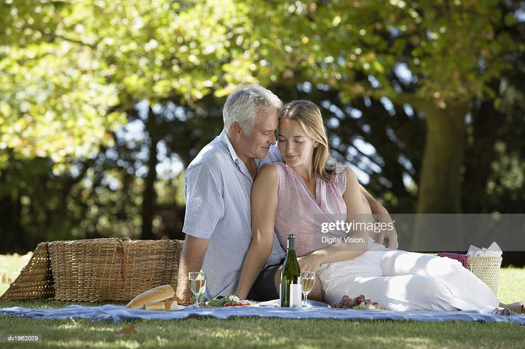 Couple Sits on a Blanket Having a Picnic : Stock Photo
